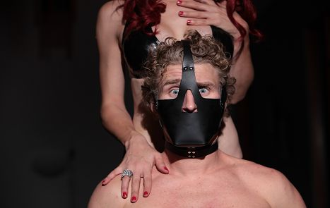 submissive man muzzled and about to be whipped